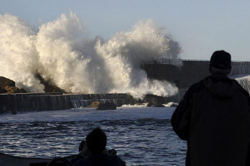 Men watch waves crash onto a breakwater, partially destroyed during last night's storm, in Cudillero, northern Spanish region of Asturias on Feb 2, 2014. A teenager was swept out to sea as fierce storm surges hit northern Spain on Sunday, authorities
