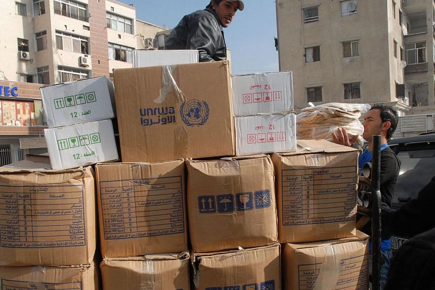 A handout picture released by the official Syrian Arab News Agency on Jan 30, 2014, shows UNRWA staff distrubuting food supplies to the residents of Syria's besieged Yarmuk Palestinian refugee camp, south of Damascus. The UN's World Food Programme (W