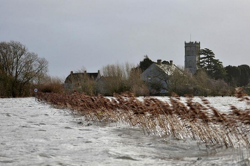 """The village of Muchelney is seen beyond flood water in Somerset, south-west England, on Jan 26, 2014.It has been nearly five weeks since the tiny village of Muchelney, which means """"great island"""" in Old English, became marooned by the floods cau"""