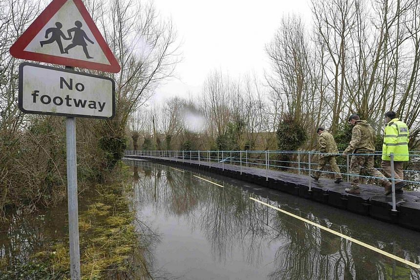 British Army Royal Engineers walk along a floating pontoon as they are shown flooded areas by Somerset Emergency Planning officer Tony Hurry (right) near the village of Muchelney on the Somerset Levels, near Langport in south-west England on Jan 30,