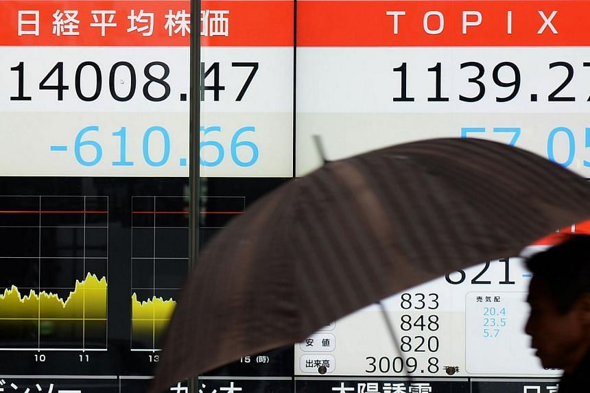 A pedestrian walks past an electronic stock display at a security company's window in Tokyo, Feb 4, 2014. Japan's Nikkei index closed down 4.18 per cent at 14,008.47 points. -- PHOTO: AGENCE FRANCE-PRESSE