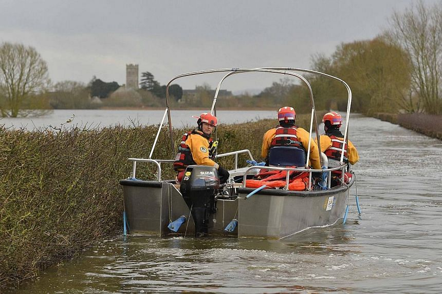 A boat operated by emergency services personnel is steered down a flooded road to the village of Muchelney on Jan 27, 2014. -- FILE PHOTO: REUTERS