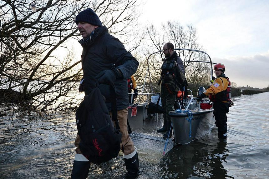 Residents disembark a boat after being transported from the cut-off village of Muchelney in Somerset, south-western England, on Jan 27, 2014. -- PHOTO: AFP