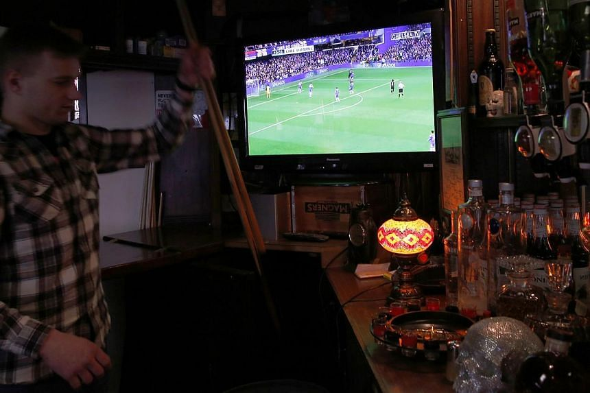A barman moves pool cues in the Yucatan Pub, with a television showing sport, in north London on Feb 3, 2014.British pubs should stay open late to screen matches in the upcoming football World Cup finals in Brazil, Prime Minister David Cameron