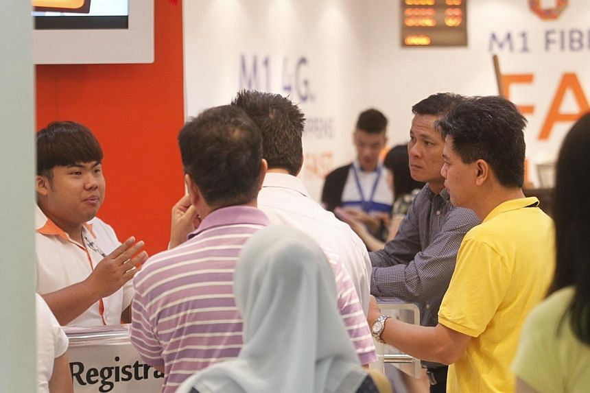 An M1 customer service personnel at the telco's outlet in Tampines Mall pacifies irate customers when the network broke down on Feb 4, 2014. -- ST PHOTO: KEVIN LIM