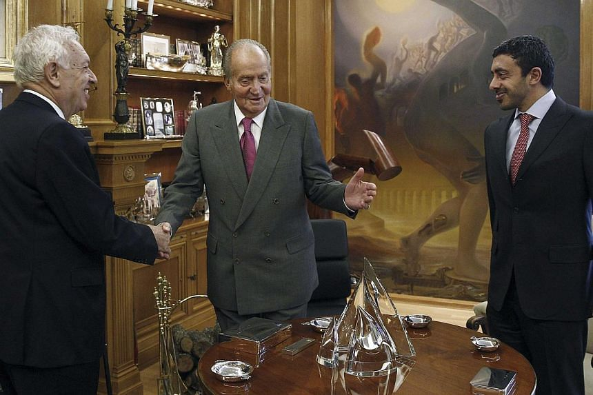 Spain's King Juan Carlos (centre) greets Spain's Foreign Minister Jose Manuel Garcia-Margallo (left) in front of United Arab Emirates (UAE) Foreign Minister Sheikh Abdullah bin Zayed al-Nahayan after their arrival at Zarzuela Palace in Madrid Feb 3,