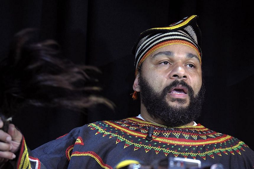 Controversial French humourist Dieudonne M'bala M'bala holds a fly-swat as he gives a press conference in the Theatre de la Main d'or in Parison Jan 11, 2014.Dieudonne on Monday answered Britain's decision to ban him from entry by giving