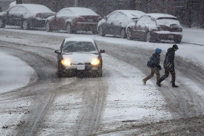 People cross a street during a snowstorm in the Brooklyn borough on Feb 3, 2014 in New York City.A fast-moving winter storm swept into the United States (US) North-east on Monday, yet again forcing flight cancellations, slowing traffic and prov