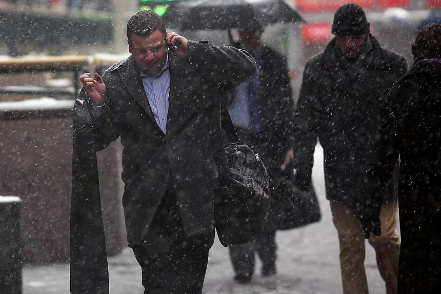 A man talks on the phone as he walks down a street during a snowstorm in Manhattan on Feb 3, 2014 in New York City. -- PHOTO: AFP