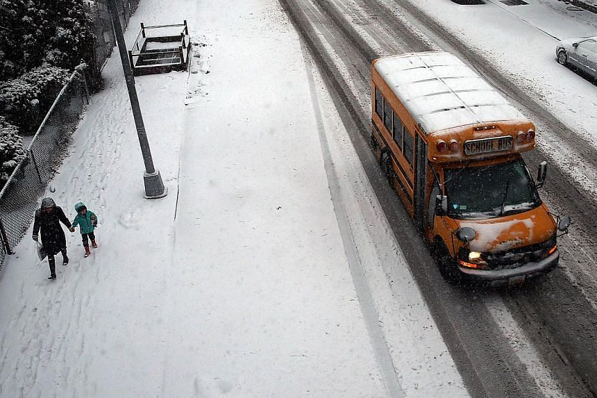 A school bus drives down a road during a snowstorm in the Brooklyn borough on Feb 3, 2014 in New York City. -- PHOTO: AFP