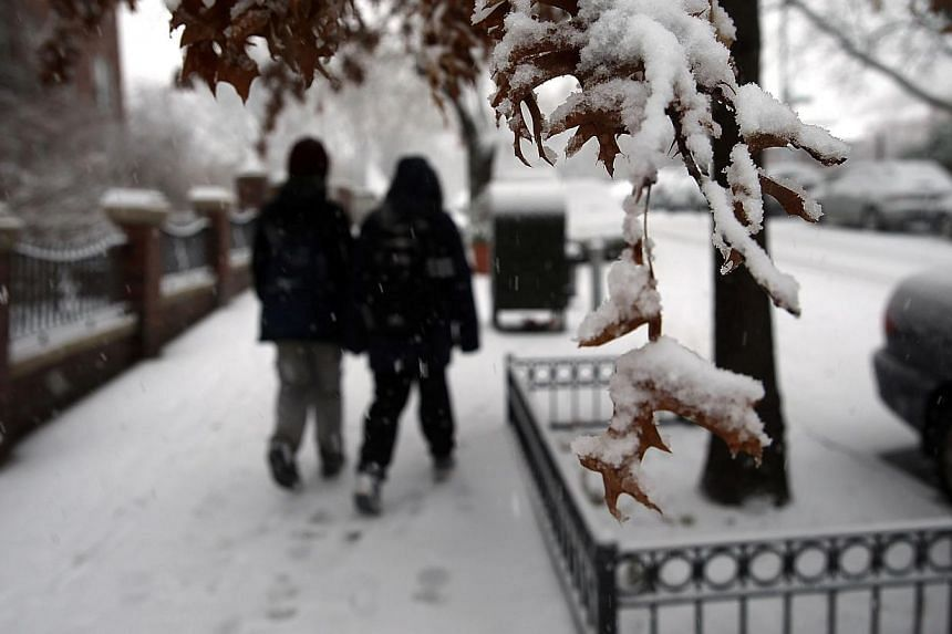 People walk down a street during a snowstorm in the Brooklyn borough on Feb 3, 2014 in New York City. -- PHOTO: AFP