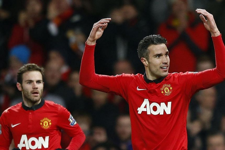 Manchester United's Juan Mata (left) looks on as teammate Robin van Persie celebrates scoring against Cardiff City during their English Premier League soccer match at Old Trafford in Manchester, northern England, on Jan 28, 2014.English footbal