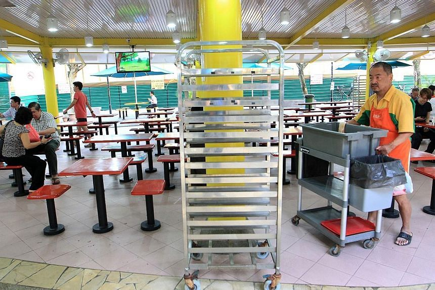 A cleaner pushing a trolley at Zion Riverside Food Centre as an empty tray return rack is seen in the centre.The National Environment Agency (NEA) has said that all tray return stands at hawker centres islandwide have to be chained securely aga