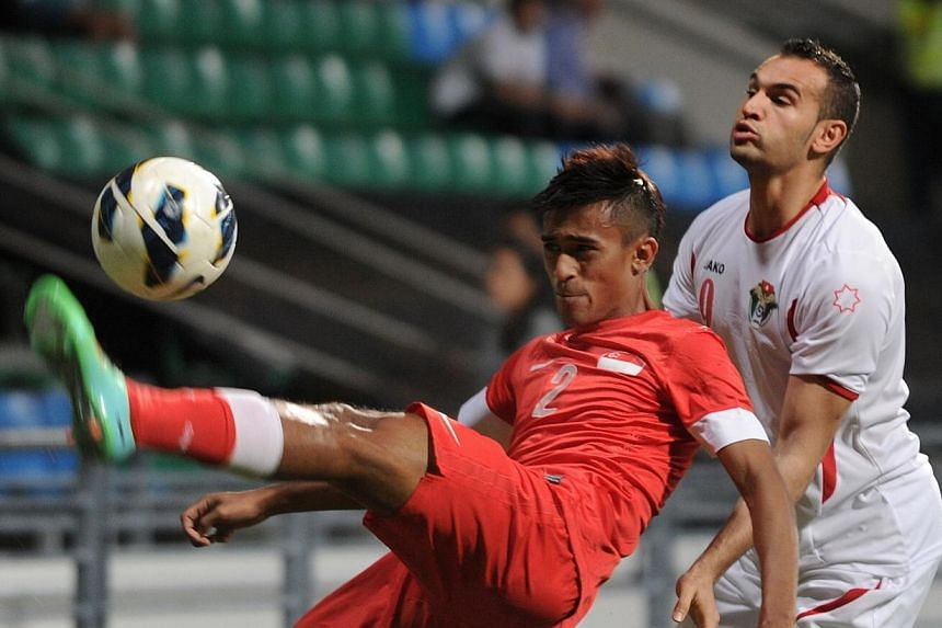 Jordanian forward Thaer Bawab (right) and Singapore defender Shakir Hamzah fight for the ball during their Asian Cup qualifier in Singapore, on Tuesday, Feb 4, 2014.Singapore suffered their fourth defeat in five Asian Cup qualifiers when they l