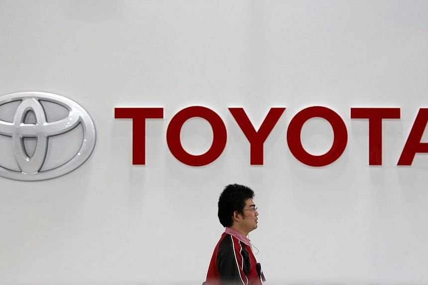 A showroom staff member walks under a logo of Toyota Motor Corp at its showroom in Tokyo, on Feb 4, 2014. -- PHOTO: REUTERS