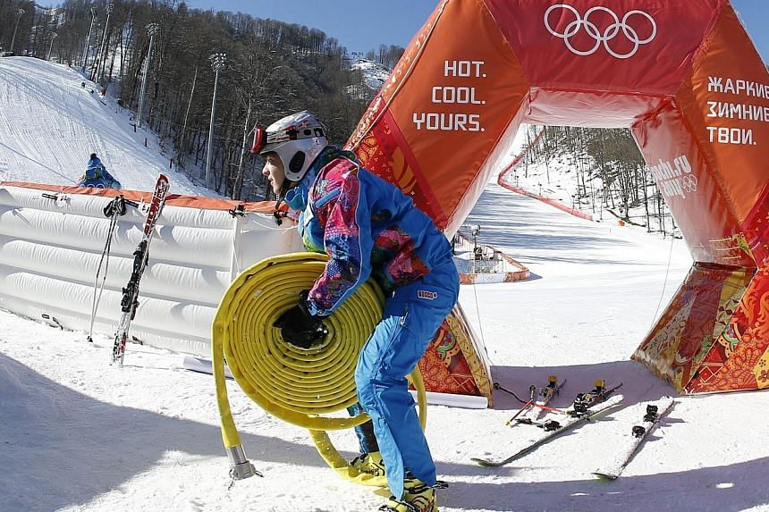 A volunteer works in the finish area of the Alpine Skiing events of the Sochi 2014 Winter Olympic Games in Rosa Khutor on Tuesday, Feb 4, 2014. Finnish snowboarder Marika Enne on Tuesday became the second crash victim of the Sochi Winter Olympic