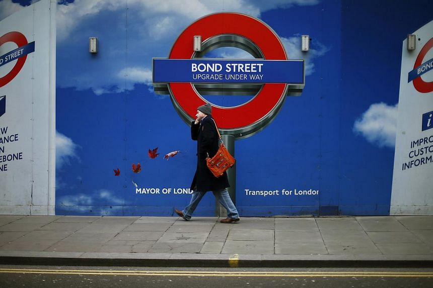 A man walks past hoardings surrounding the building work at London Underground's Bond Street station in central London on Jan 27, 2014.London faces travel chaos on Tuesday when workers on the Underground railway go on strike for 48 hours to pro