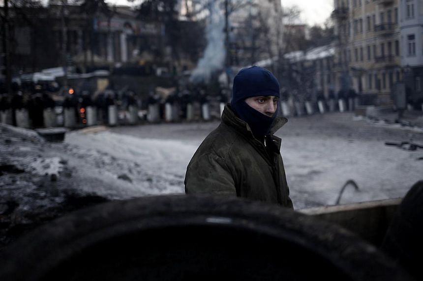 "An anti-government protester stands near a road block barricade in Kiev on Feb 3, 2104. Ukraine's President Viktor Yanukovych blasted mass protests against his rule as ""extremism"" on Monday, Feb 3, 2014, as the European Union and United States m"
