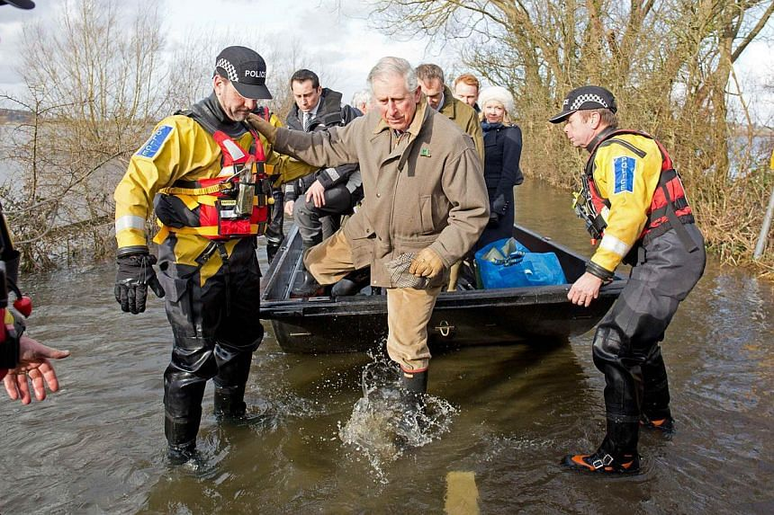 Britain's Prince Charles (centre) is assisted by police officers as he gets off a boat run by Avon and Somerset police upon arriving in Muchelney on Feb 4, 2014. More bad weather left thousands of British homes without power on Tuesday, hours after P