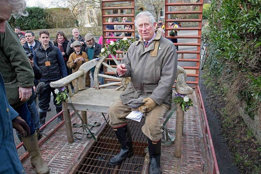 Britain's Prince Charles sits on a decorated garden bench as he travels in a trailer through flood water in Muchelney, on route to Thorney Moor Farm on Feb 4, 2014. -- PHOTO: REUTERS