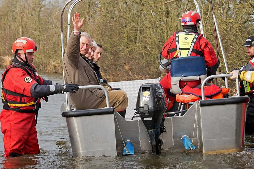 Britain's Prince Charles (second, left) waves as he leaves on a boat run by the Bridgewater Fire Service, in Muchelney on Feb 4, 2014. -- PHOTO: REUTERS