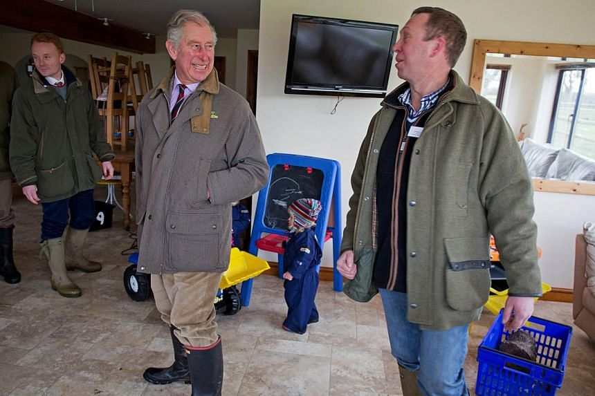 Britain's Prince Charles (second, right) smiles as he stands in Chris Curtis' lounge in Thorney Moor Farm on Feb 4, 2014. -- PHOTO: REUTERS