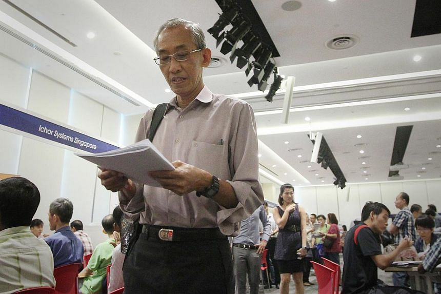 An older man looking at forms at a job fair last month. Singaporeans need to move away from viewing job seekers in their 40s, 50s and 60s as ''over the hill'', says the writer. Most of them are not, and are far from it. Job seekers must also acknowle
