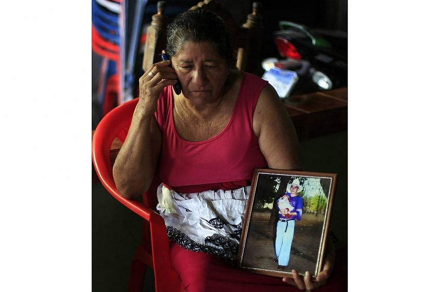 Mrs Maria Julia Alvarenga, mother of castaway Jose Salvador Alvarenga, talks on the phone while showing a photograph of his son, in their fishing hometown of Ahuchapan on Feb 4, 2014. -- PHOTO: REUTERS
