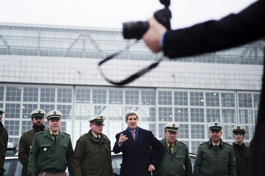 "US Secretary of State John Kerry (centre) poses with German policemen before boarding his plane at Franz-Josef-Strauss Airport in Munich, southern Germany, on Feb 2, 2014. Secretary of State John Kerry Tuesday hit out the ""brutality"" of the Syri"