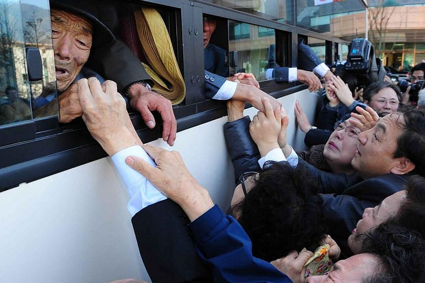 In a file picture taken on Nov 1, 2010, North Koreans (in the bus) grip hands of their South Korean relatives as they bid farewell following their three-day separated family reunion meeting at Mount Kumgang resort. North and South Korea agreed on Wed