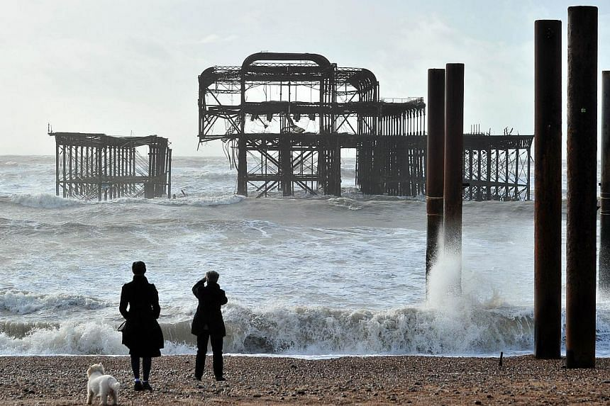 Brighton's West Pier in southern England is divided into two parts after rough seas caused a section on the east side to collapse, on Feb 5, 2014. More than 8,000 homes were without power in southwest England on Wednesday, Feb 5, 2014, after fresh st