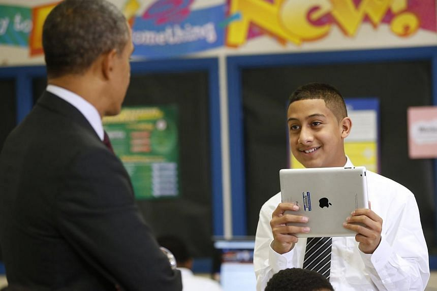 A student using an iPad looks up at US President Barack Obama who was visiting Buck Lodge Middle School in Adelphi, Maryland on Feb 4, 2014. Mr Obama has a pen. He has a phone. And on Tuesday, he wielded an iPad to help make a point about how he