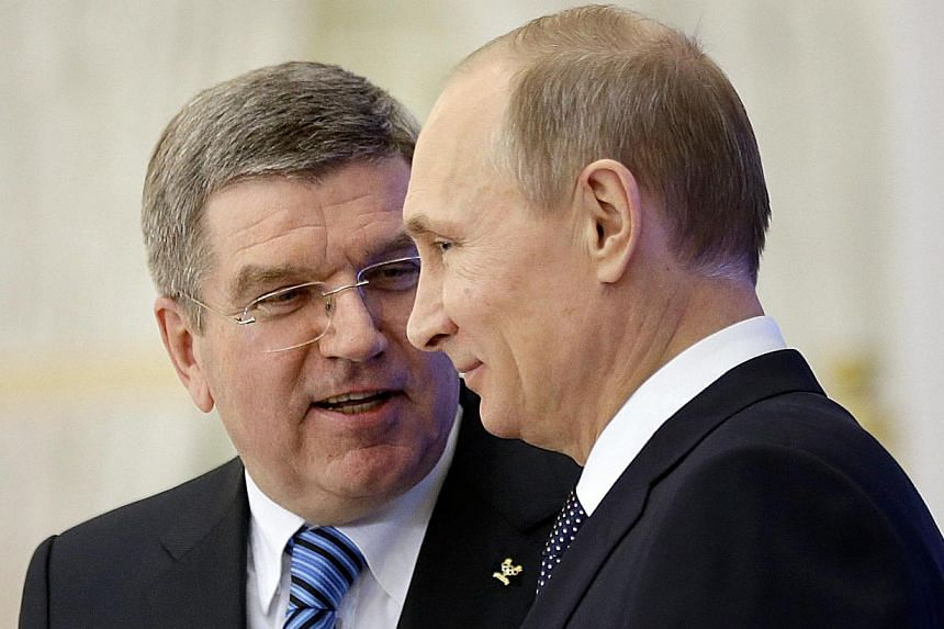Russian President Vladimir Putin (right) and International Olympic Committee (IOC) President Thomas Bach step off the podium after speaking at an event welcoming IOC members ahead of the upcoming 2014 Winter Olympics at the Rus Hotel in Sochi, on Feb