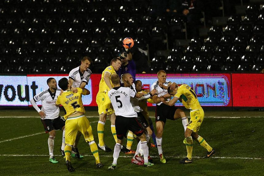 Sheffield United goalkeeper David Stockdale (centre) punches the ball clear during their English FA Cup soccer match against Fulham at Craven Cottage in London on Feb 4, 2014. Sheffield United scored in the last minute of extra time to dump sorr