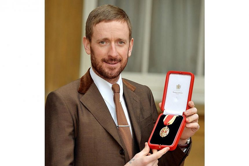 British cyclist Bradley Wiggins poses for a photograph with his Knighthood medal, awarded to him by Queen Elizabeth during an Investiture ceremony at Buckingham Palace in central London.Bradley Wiggins has revealed that his children had to move