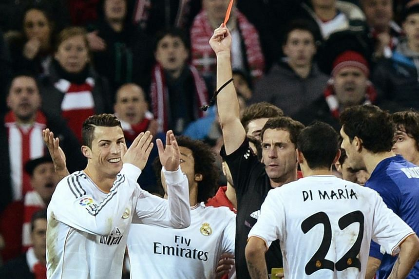 Real Madrid's Cristiano Ronaldo (left) laughs as he receives a red card during their Spanish first division soccer match against Athletic Bilbao at San Mames stadium in Bilbao, on Feb 2, 2014.Recently crowned Ballon d'Or winner Cristiano Ronald