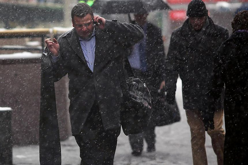A man talks on the phone as he walks down a street during a snowstorm in Manhattan on Feb 3, 2014, in New York City. -- FILE PHOTO: AFP