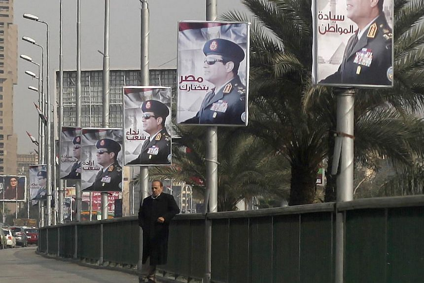 A man stands on a bridge where huge posters of Egypt's Army chief Field Marshal Abdel Fattah al-Sisi are hanged in central Cairo on Feb 3, 2014. Egypt's top military commander Abdel Fattah al-Sisi said in comments published in Kuwait on Thursday that