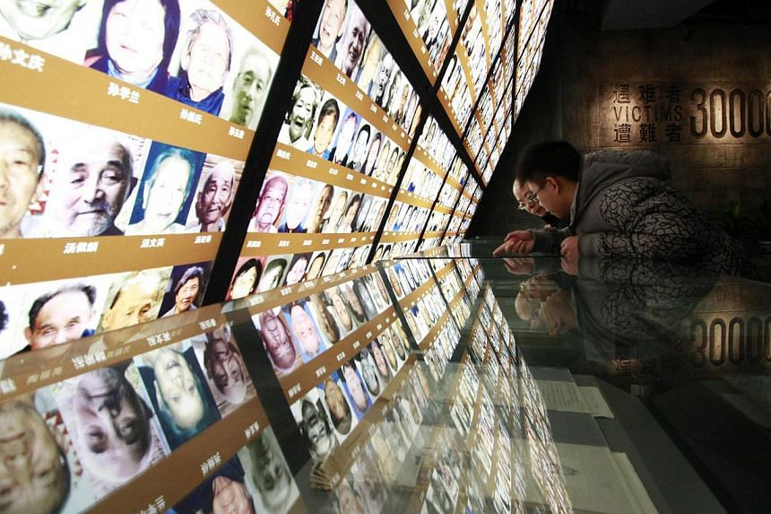 Visitors lean on an exhibition stand ahead of 76th anniversary of the start of the Nanjing Massacre at the Nanjing Massacre Museum in Jiangsu province last year. -- PHOTO: REUTERS