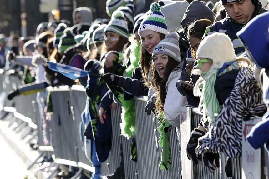 Fans stand along 4th Avenue at the Super Bowl victory parade for the Seattle Seahawks in downtown Seattle, Washington, on Feb 5, 2014. -- PHOTO: REUTERS