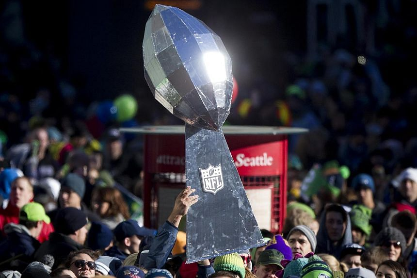 A Seattle Seahawks fan holds a giant Lombardi Trophy Super Bowl during the NFL team's Super Bowl victory parade in Seattle, Washington, on Feb 5, 2014. -- PHOTO: REUTERS