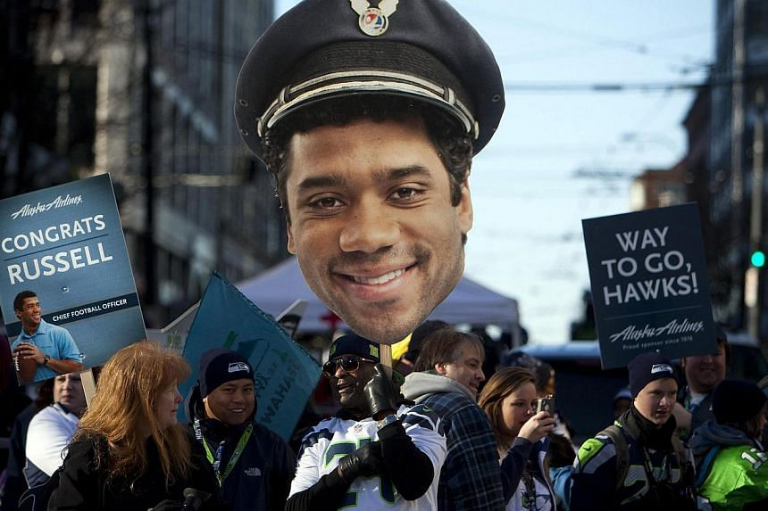 A fan holds a cut out of Seattle Seahawks quarterback Russell Wilson during the NFL team's Super Bowl victory parade in Seattle, Washington, on Feb 5, 2014. -- PHOTO: REUTERS