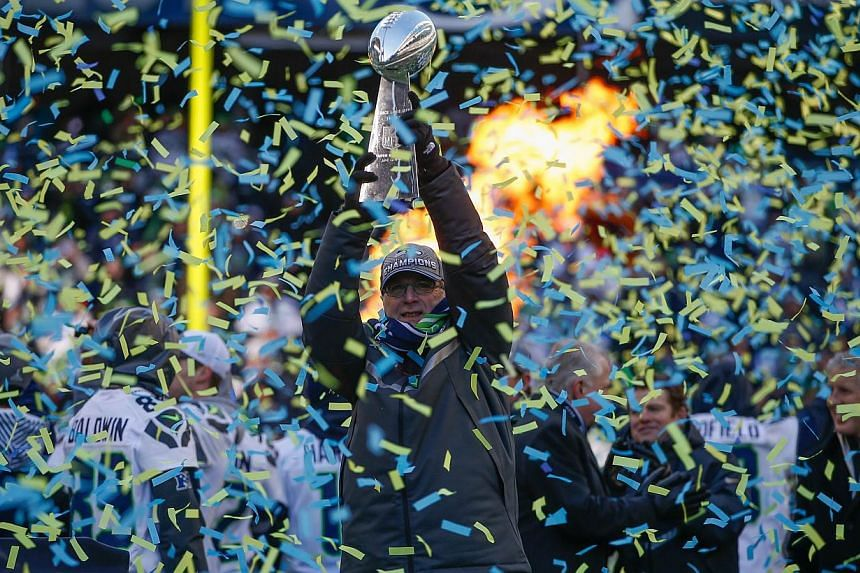 Team owner Paul Allen of the Seattle Seahawks holds the Lombardi Trophy during ceremonies following the Super Bowl XLVIII Victory Parade at CenturyLink Field in Seattle, Washington, on Feb 5, 2014. -- PHOTO: REUTERS