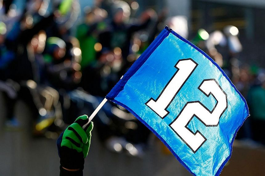Fans wave the 12th Man flag to celebrate Seattle Seahawks victory in Super Bowl XLVII during a parade in Seattle, Washington, on Feb 5, 2014. -- PHOTO: AFP