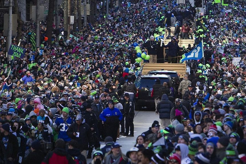 Seattle Seahawks' players celebrate with fans during the NFL team's Super Bowl victory parade in Seattle, Washington, on Feb 5, 2014. -- PHOTO: REUTERS