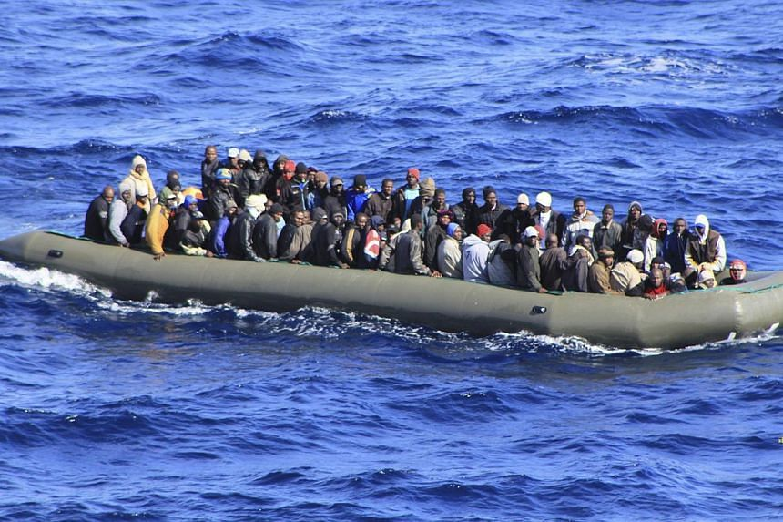 Migrants are seen in a boat during a rescue operation by Italian navy ship San Marco off the coast to the south of the Italian island of Sicily, on Feb 5, 2014. The Italian navy has rescued more than 1,100 migrants from nine large rafts in the waters