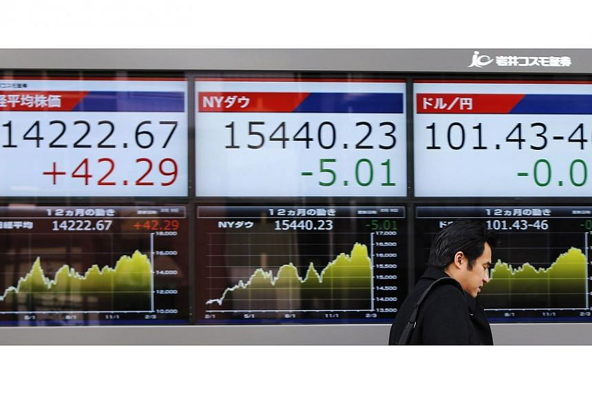 A pedestrian walks past electronic boards showing Japan's Nikkei average (Left), Dow Jones Industrial Average (Center) and the exchange rates between the Japanese yen and the U.S. dollar, outside a brokerage in Tokyo, on Feb 6, 2014.Asian markets mos