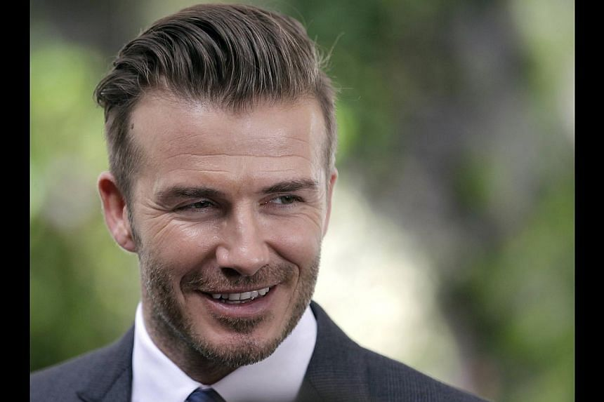 David Beckham smiles after a news conference in Miami, Florida on Feb 5, 2014. Two of the biggest names in world sport over the past decade could yet team up in Miami, if David Beckham gets his way. -- PHOTO: REUTERS