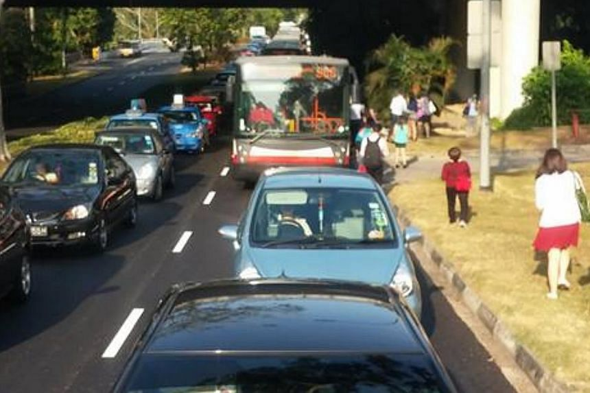 Commuters caught in the jamon the Bukit Timah Expressway (BKE)alight from buses.Traffic came to a standstill on the BKE in the direction of the Pan Island Expressway (PIE) at the Bukit Panjang Road entrance during the morning rush h
