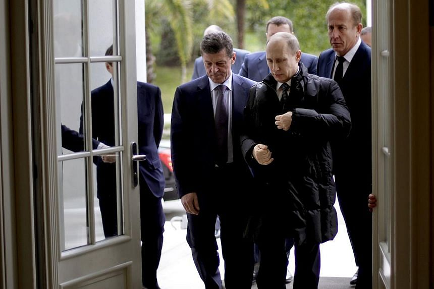 Russian President Vladimir Putin (Right) arrives with Deputy Prime Minister Dmitry Kozak (Left) for a welcoming event for International Olympic Committee (IOC) members ahead of the upcoming 2014 Winter Olympics at the Rus Hotel on Feb 4, 2014 in Soch